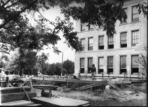 Primary view of object titled '[Fort Bend County Courthouse addition construction, lumber and tools to the left]'.