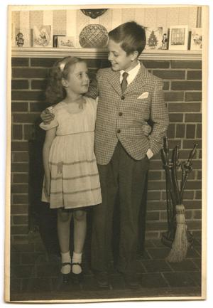 Primary view of object titled 'Photo of boy and girl in front of fireplace'.
