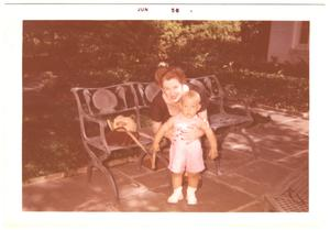 [Lillie Abercrombie with toddler on patio bench]