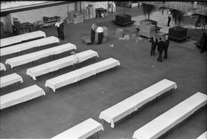 Primary view of object titled '[Banquet tables being set up at the Dallas Trade Mart]'.