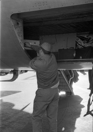 Primary view of object titled '[An airport worker putting cases in the luggage compartment of a plane]'.