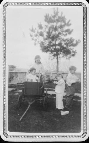 Primary view of object titled '[Children standing around a child in a wagon at Mary Dee and August Myers home]'.