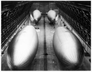 Primary view of object titled '[Four K-type airships docked in the hangar at Hitchcock Naval Air Station]'.