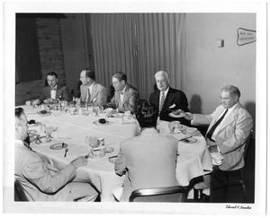 [Lamar Fleming Jr. seated at formal breakfast with unidentified men]