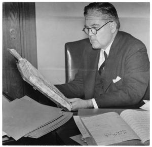 Primary view of object titled '[George A. Hill, Jr. sitting at desk reading book]'.