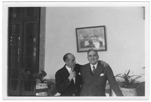 [George Alfred Hill, Jr. with unidentified man in room with potted plants]