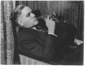 Primary view of object titled '[George A. Hill, Jr. leaning back in armchair, cigar in hand]'.