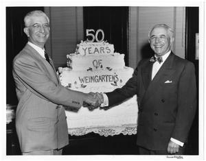 Primary view of object titled '[Abe and Joe Weingarten shaking hands in front of 50 years of Weingarten's cake]'.