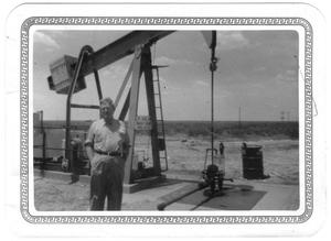 Primary view of object titled '[Lamar Fleming, Jr. posed in front of oil well with sign L. F. Oil Co.]'.