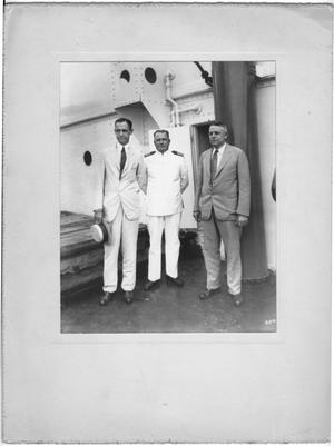 [Three unidentified men, one dressed as naval officer in front of doorway]
