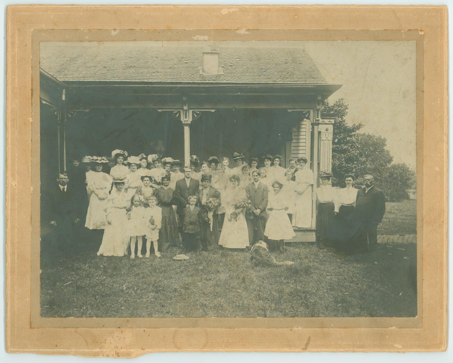 [Howard and Carter Wedding Party], Photograph of the wedding party of Kathleen Howard and Joseph D. Carter of Longview, Texas. There are several unidentified family members and guests in the photograph; all known members are listed on the back of the photograph. From left to right, top to bottom, the members pictured are: Top row: Luke Cole, Mrs. Joe Battle, Birdie Fisher, Bo Brown, Garland Smith, Tracy Flanagan, Flo Bramlette, Sadie Spradling, Anita Howard, Mr. and Mrs. J. D. Roach. Second row: Anna Coleman, Mrs. W. F. Wood, Camie F. Gray, Joseph D. Carter, Kathleen Howard, Laura Howard, Mr. McGinnis, Gladys Howard, Mr. and Mrs. Jackson C. Howard (parents of the bride). Bottom row: Agnes Brown, W. C. Hixson, Shep (family dog).,