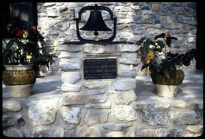 [Bell, Plaque, and Flower Vases on Stone Construction]