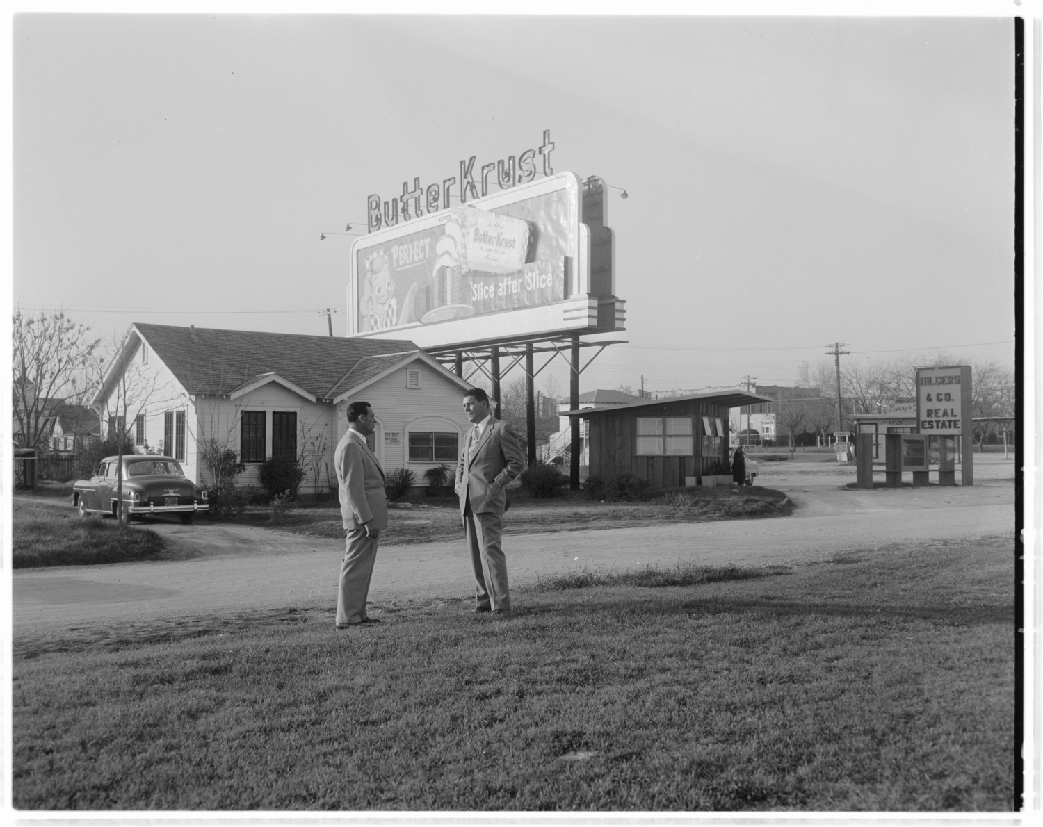 [Two men standing across the road from a Butter Krust billboard]                                                                                                      [Sequence #]: 1 of 1
