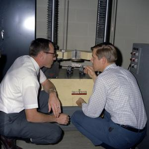 Two Unidentified Men with measuring Tools