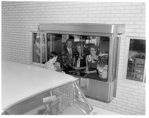 Primary view of object titled '[Man and women assisting customer at drive-up window]'.