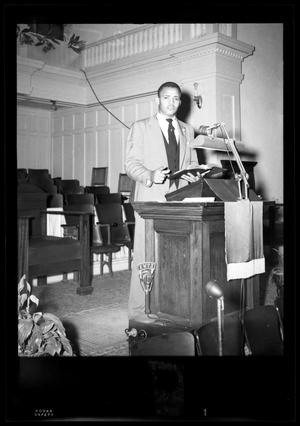 Primary view of object titled '[Photograph of a Man Standing Behind a Podium]'.