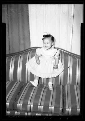 Primary view of object titled '[Photograph of a Young Child Standing on a Couch]'.