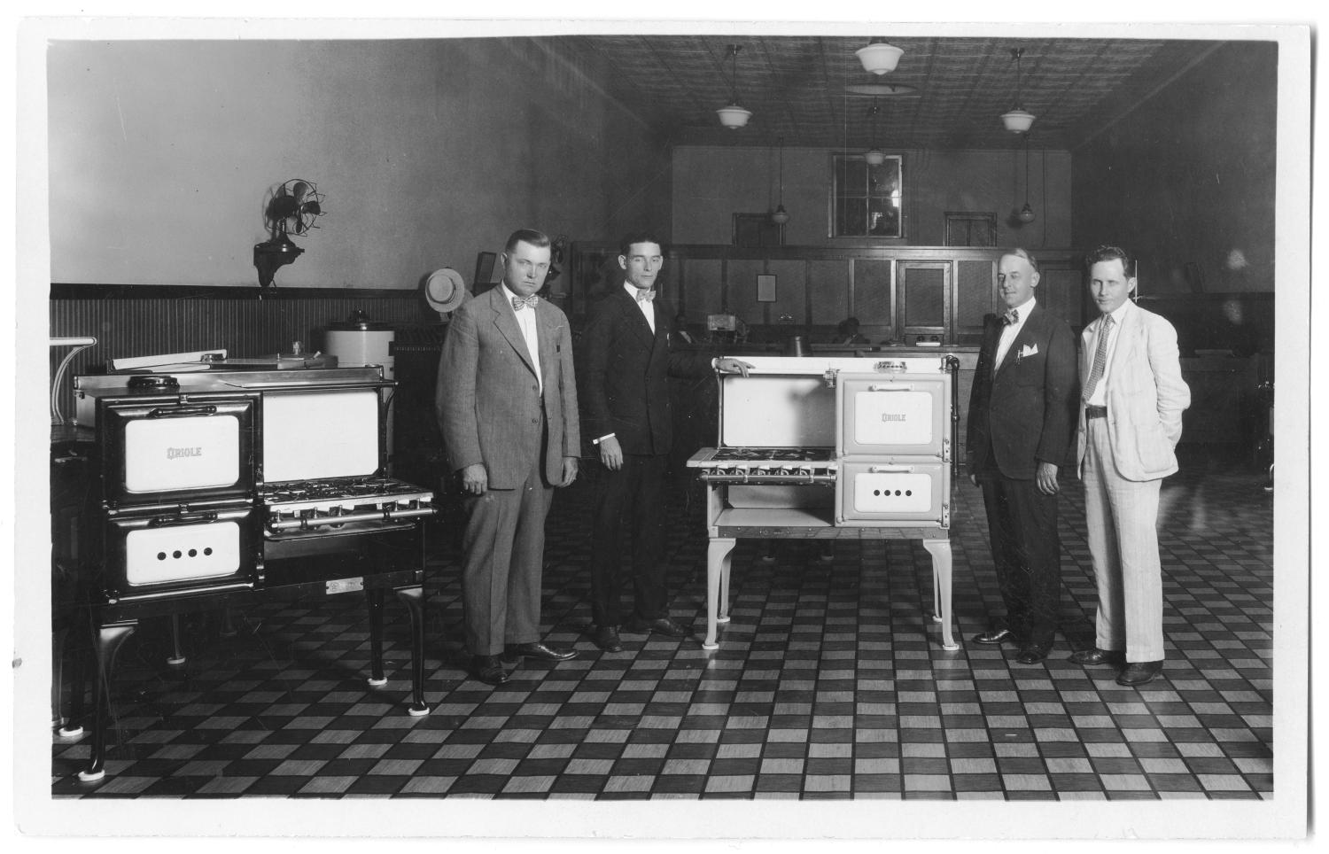 [Men Standing With Gas Ranges], Photograph of four men standing with gas ranges inside a store, from Peoples Gas Co. The men are wearing suits and ties, and are looking towards the camera. There is one black gas range on the left, and one white one in the middle of the photograph. There is a stamp on the back from Papsons Studio.,