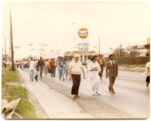 Primary view of object titled '[People Marching Past Gas Station]'.