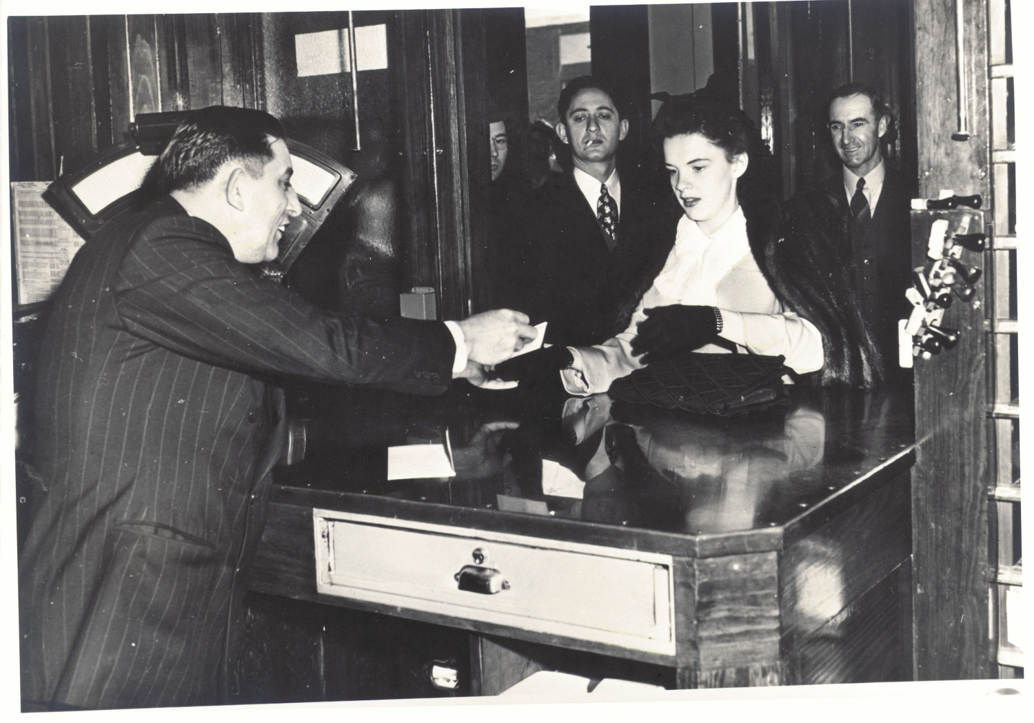 """[Judy Garland in Mineral Wells], This picture, found on page 161 of """"Time Was..."""" by A. F. Weaver, identifies the man selling a money order to Judy Garland in the Old Post Office (on NE 2nd Street) as D. C. Harris. The man on the right is identified as W. A. Ross. It has since [2102] been determined that the reason for Miss Garlands presence in the post Office was to lead a procession of children there in order to purchase Defense Stamps.,"""