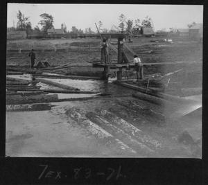 "Primary view of object titled '[Southern Pine Lumber Company Mill Ponder Workers at the Bottom of the ""Endless Chain""]'."