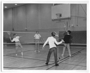[Photograph of Students Playing Badminton in a School Gymnasium]