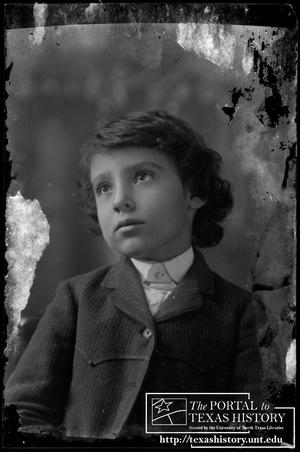 [Young boy in a pin-striped suit with western yoke detailing]