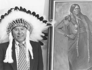 Primary view of object titled 'Vance Tahmahkera Standing by a Portrait of Quanah Parker'.