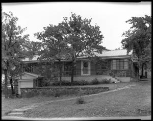 Primary view of object titled '[Unidentified stone building with garage and walkway]'.