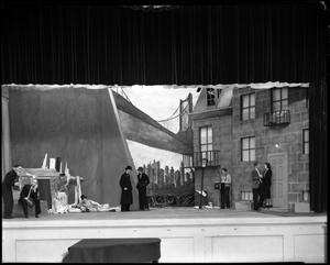 [Actors performing in front of a cityscape drama set]