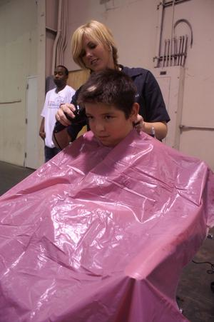 [Barber cuts the hair of a young man during a back to school fair]