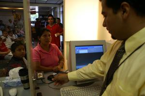 Primary view of object titled '[Woman and boy waiting at counter with man behind computer]'.