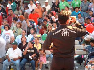 Primary view of object titled '[Photo from behind man with microphone facing crowd]'.