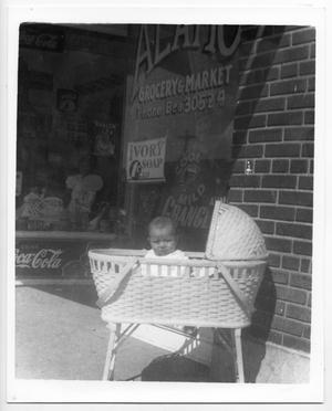 [Baby in bassinet in front of Alamo Grocery store]