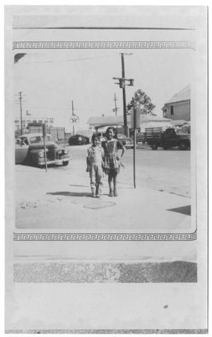 [Boy and girl in front of street with Texaco Station]