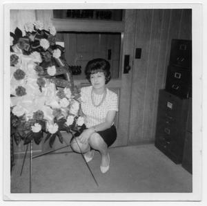 Primary view of object titled '[Bernice Kinkaid posing next to floral arrangement]'.