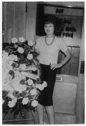 Primary view of object titled '[Bernice Kinkaid standing next to floral arrangement]'.
