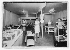 Primary view of object titled '[Photograph of women and a man standing in a bakery]'.