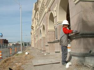 Primary view of object titled '[Workman smooths cement on the front of the new Fort Worth Mercado building]'.