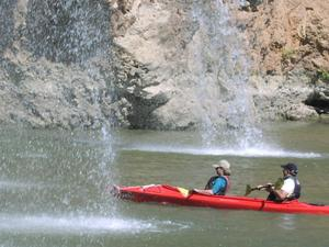 [Two people in a kayak approach a double waterfall]