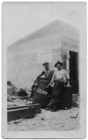 Primary view of object titled '[Two Men in Front of Wooden Building]'.