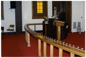 Primary view of object titled '[Silver Communion Cups Lining a Wooden Banister Inside Danevang Lutheran Church]'.