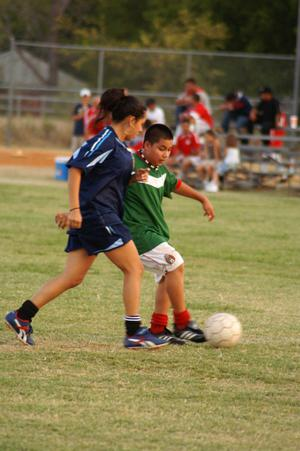 Primary view of object titled '[Boy and girl playing soccer]'.