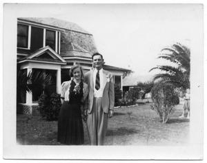 Primary view of object titled '[Young Woman and Man in Front of House]'.