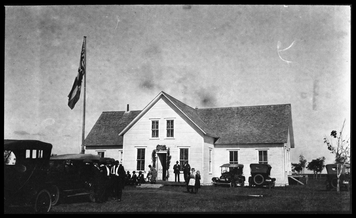 Danevang Lutheran Church, Copy negative of Danevang Lutheran Church in Danevang, Texas. Several groups of people are standing outside the church; some are sitting on the porch while others are standing near parked automobiles. Two flags, one American and one Texan, fly over the church, and a floral garland hangs over the front door.,