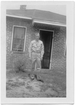 Primary view of object titled '[Melvin Hansen in Front of Brick House]'.
