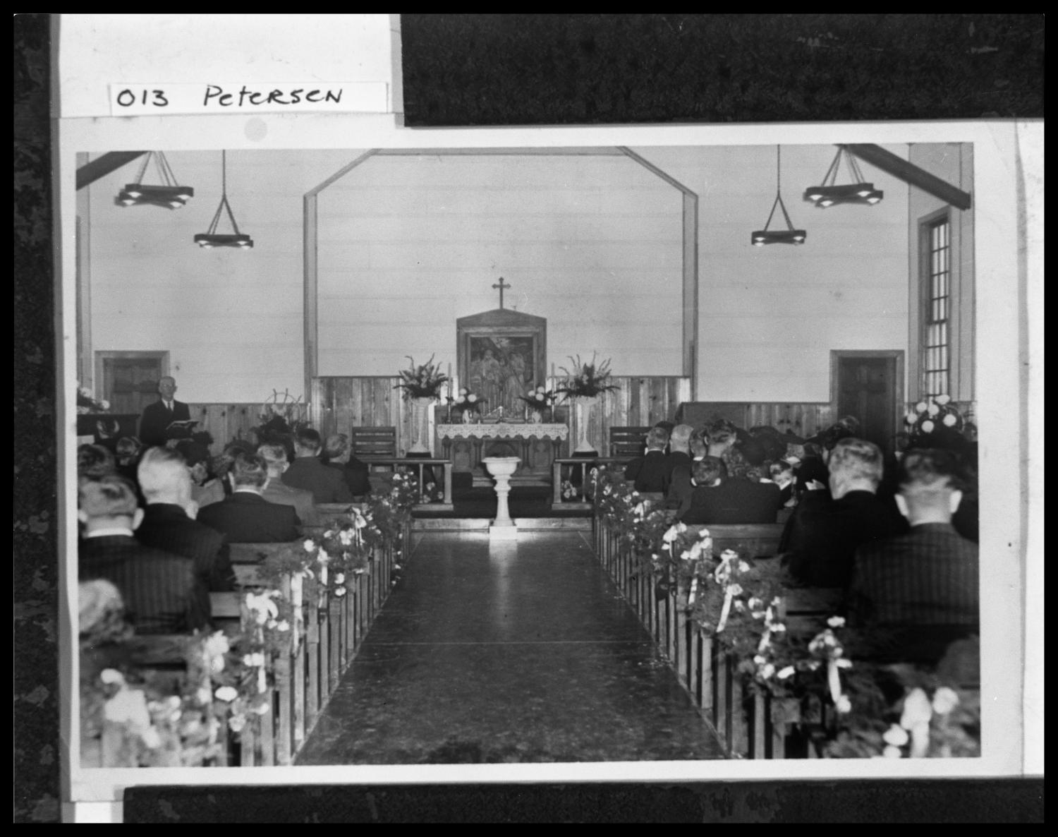 [Interior of Danevang Lutheran Church], Copy negative of a black and white photograph of the Danevang Lutheran Church interior. Two columns of wooden pews that have decorative garland attached to them lead up to an altar at which a small baptismal fount sits between two banisters. Floral arrangements and a painting with a cross atop its frame adorn the center of the altars alcove. Members of the congregation fill the pews. Light fixtures hang from the interiors rafters above the congregation.,