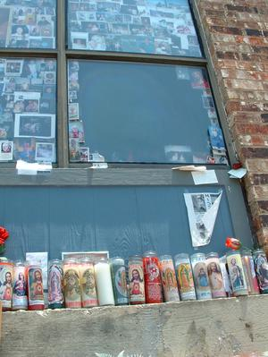 [Candles and photographs surround the window where the Virgin Mary was sighted]