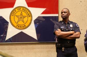 Primary view of object titled '[A Police Officer Stands Beside a Framed City of Dallas Flag]'.
