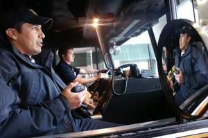 Primary view of object titled '[Two firemen sit in the front seat of the fire engine, one driving, the other holding a two-way radio]'.